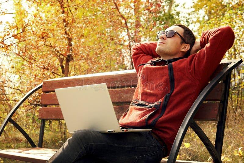 Homem maduro feliz que usa o portátil ao sentar-se na cerca contra o lago Novo ele especialista para tomar uma ruptura do trabalh imagens de stock royalty free