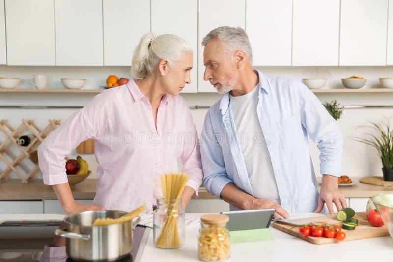 Homem maduro irritado que está perto da mulher séria madura na cozinha fotografia de stock