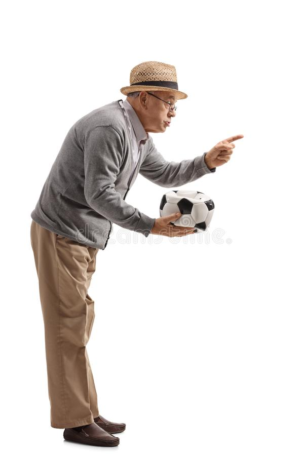 Homem maduro irritado que guarda um futebol desinflado e que discute o someon foto de stock