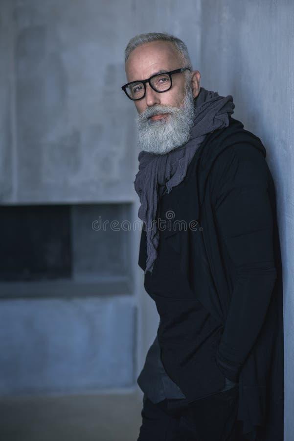 Homem maduro não barbeado sereno que localiza no apartamento imagem de stock