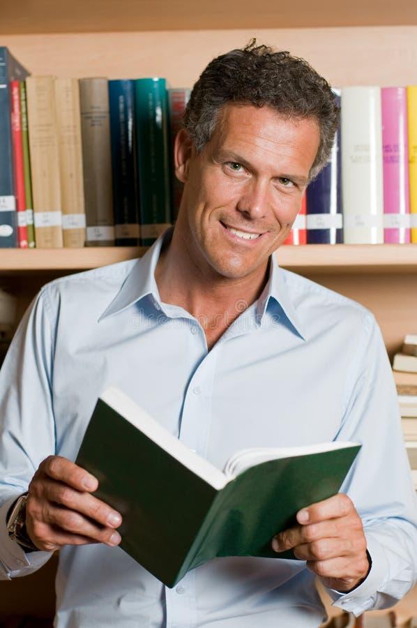 Homem maduro na biblioteca foto de stock