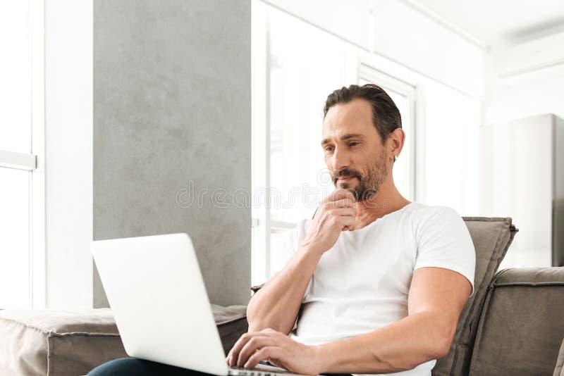 Homem maduro pensativo que senta-se em um sofá fotos de stock royalty free