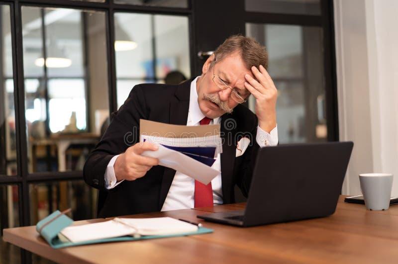 Homem maduro preocupado sério que calcula contas para pagar ou que verifica as finanças domésticas forçadas dos documentos do déb imagem de stock royalty free