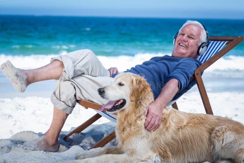 Homem maduro que descansa em uma cadeira de plataforma que escuta trocas de carícias da música seu cão imagens de stock