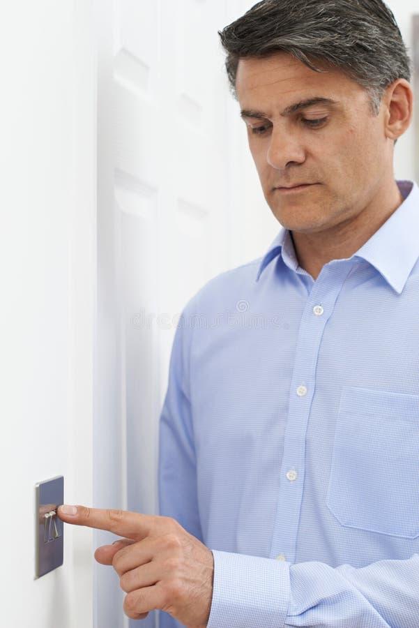 Homem maduro que desliga o interruptor da luz em casa fotografia de stock