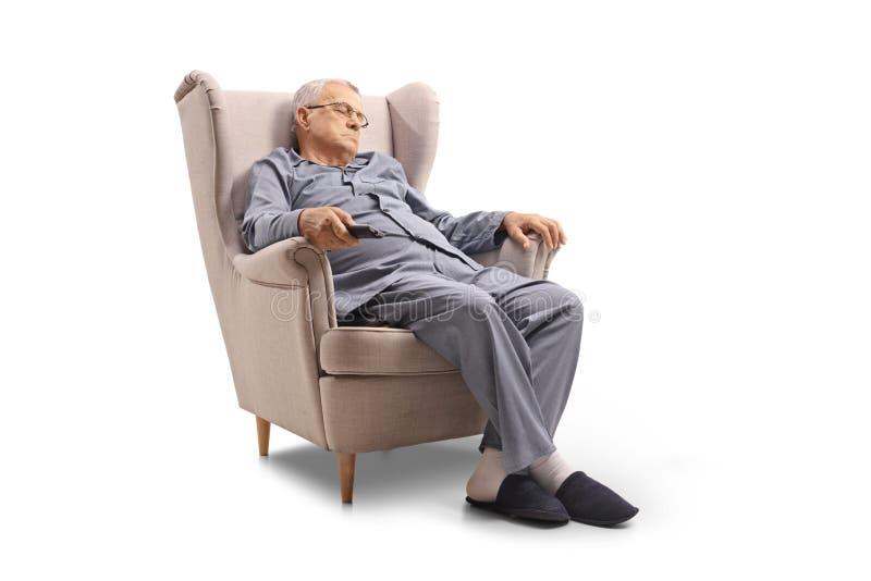 Homem maduro que dorme em uma poltrona imagem de stock
