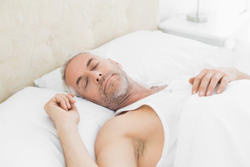 Homem maduro que dorme na cama em casa imagem de stock royalty free