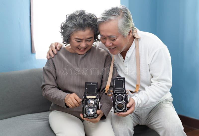 Homem maduro que ensina sua esposa usar uma câmera do filme do vintage na sala de visitas foto de stock royalty free