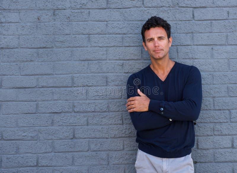 Homem maduro que está contra a parede cinzenta com os braços cruzados fotografia de stock royalty free