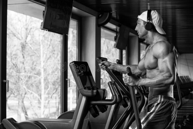 Homem maduro que faz a ginástica aeróbica Walker In Gym elíptico foto de stock royalty free