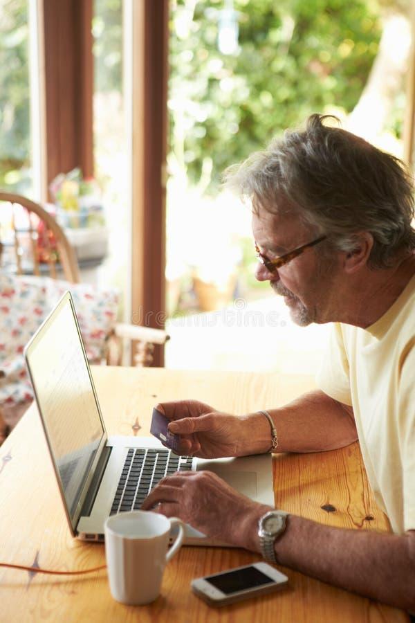 Homem maduro que faz na linha compra usando o cartão de crédito imagens de stock royalty free