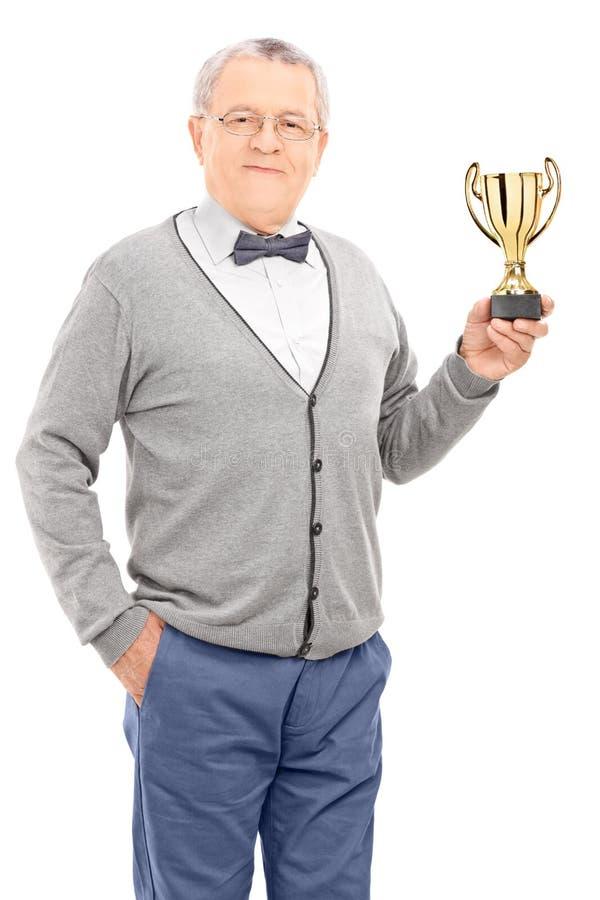 Homem maduro que guarda um troféu fotografia de stock
