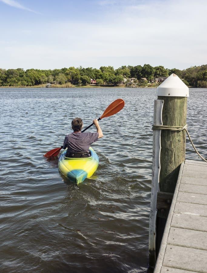 Homem maduro que Kayaking para o divertimento e a aptidão foto de stock
