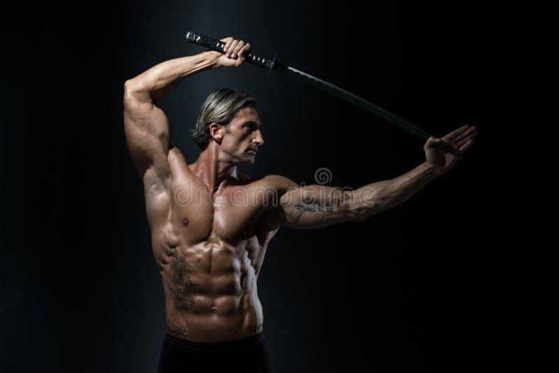 Homem maduro que mantém a espada pronta para lutar imagem de stock