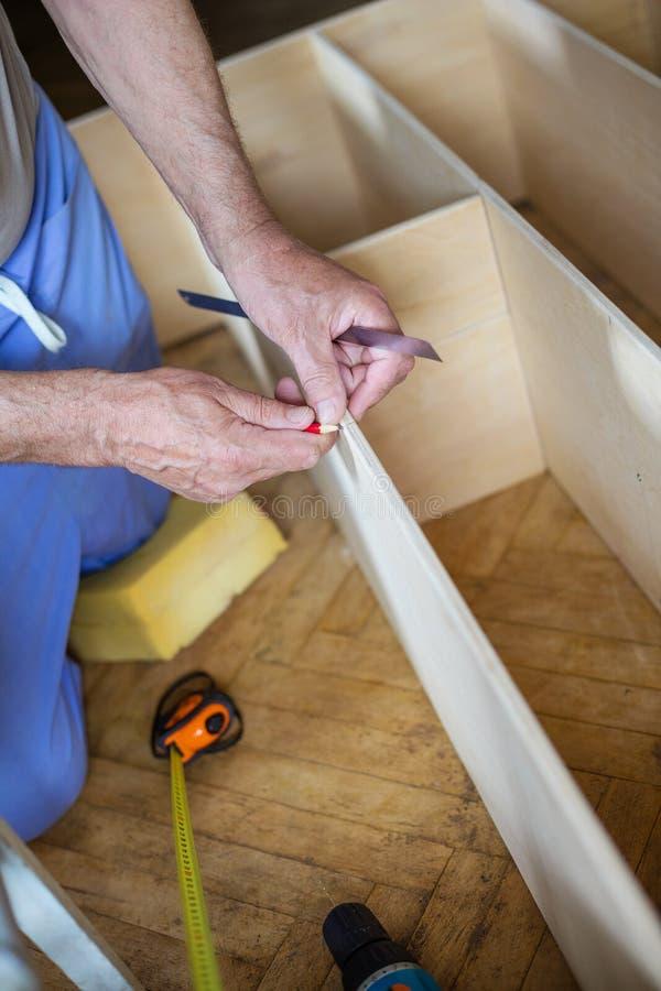 Homem maduro que mede a prateleira de madeira com medida da fita e que faz m fotos de stock