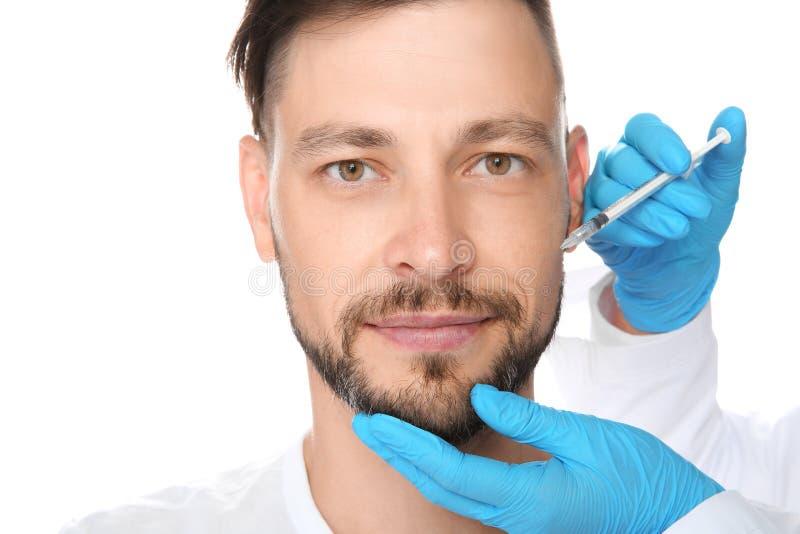 Homem maduro que obtém a injeção facial no fundo branco imagem de stock royalty free