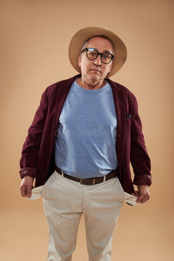 Homem maduro que olha a virada e que mostra seus bolsos vazios imagem de stock royalty free