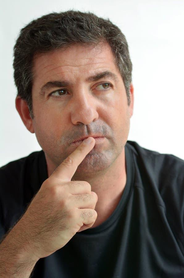 Homem maduro que pensa com o um dedo em seus bordos fotos de stock