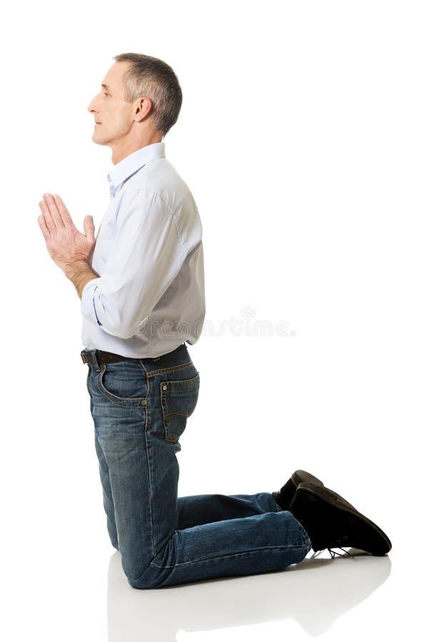 Homem maduro que reza ao deus em joelhos fotos de stock