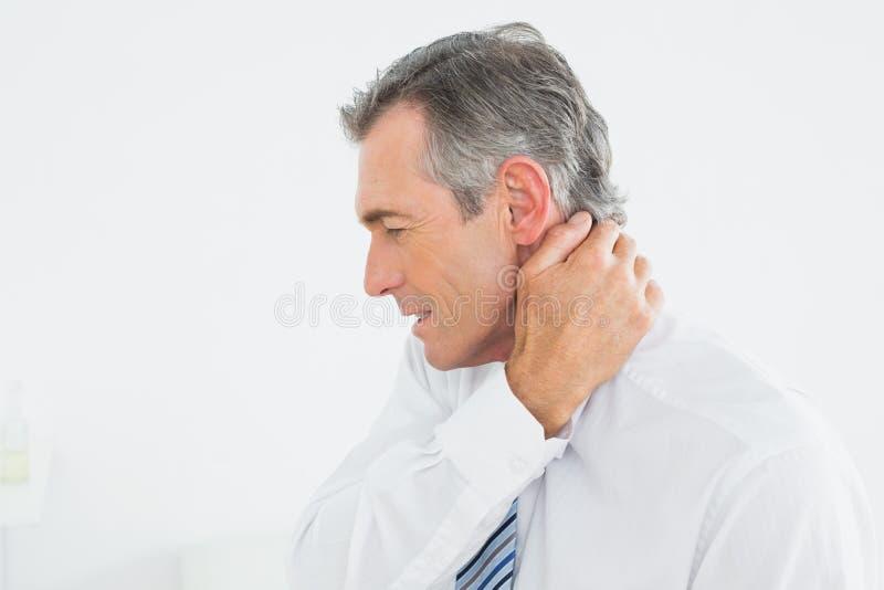 Homem maduro que sofre da dor de pescoço imagens de stock royalty free