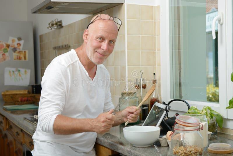 Homem maduro que sorri na cozinha fotos de stock