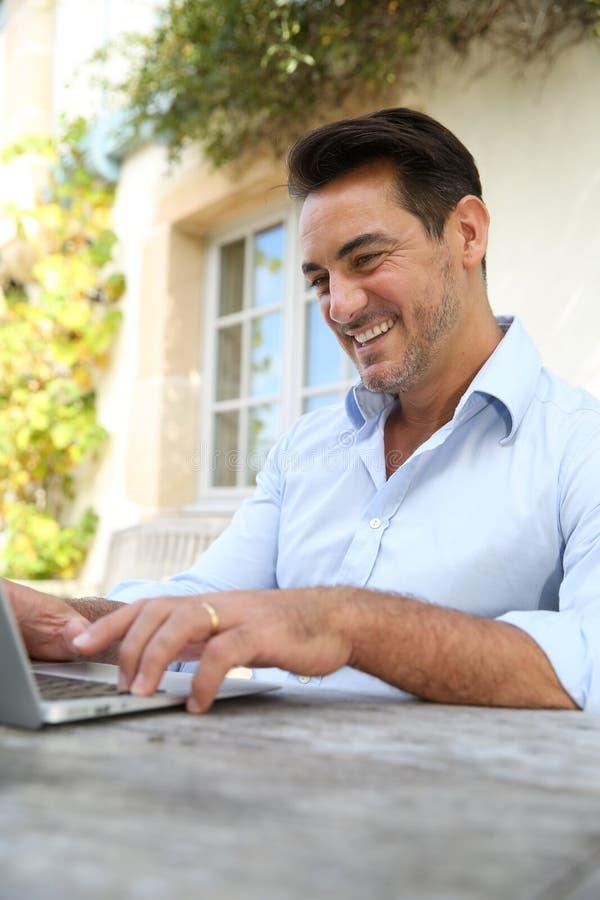 Homem maduro que teleworking fora imagem de stock royalty free