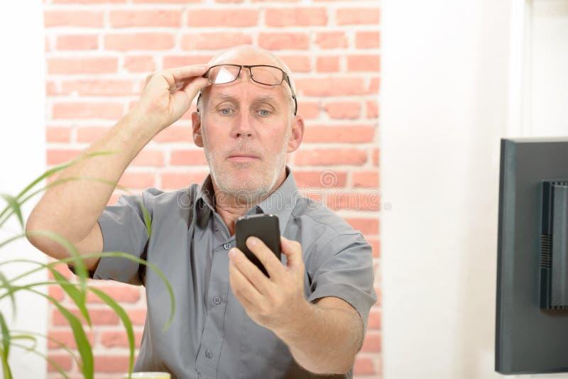 Homem maduro que tem o problema que vê a tela do telefone imagens de stock