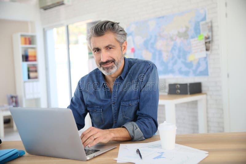 Homem maduro que trabalha em seu portátil fotos de stock royalty free
