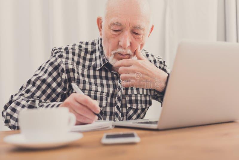 Homem maduro que usa o portátil e escrevendo no bloco de notas fotografia de stock