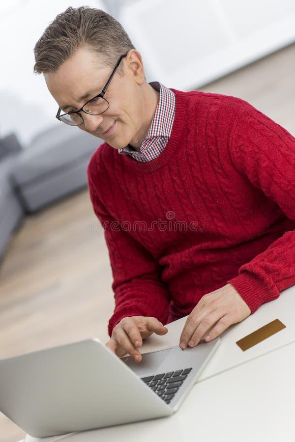 Homem maduro que usa o portátil na tabela na casa fotos de stock