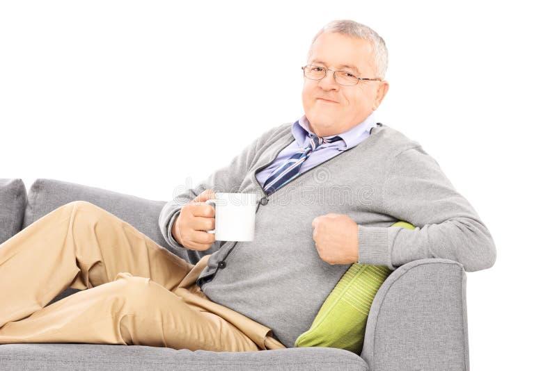 Homem maduro relaxado que coloca no sofá e no chá bebendo foto de stock royalty free