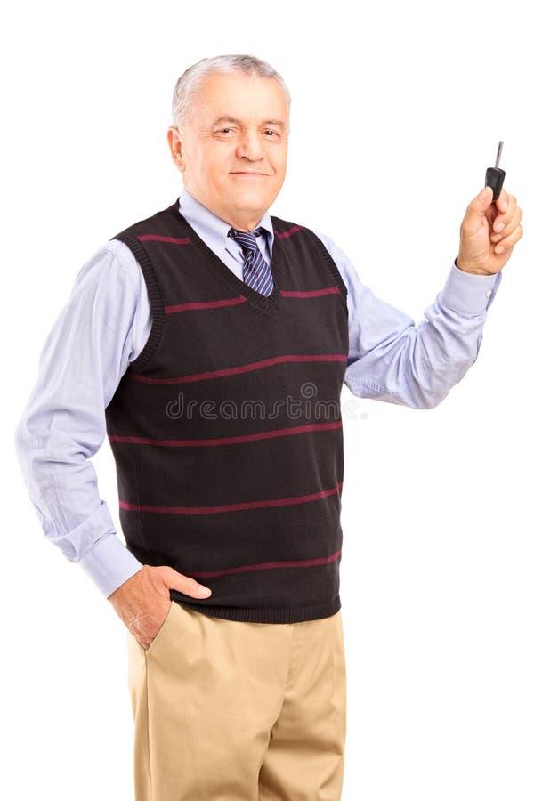 Homem maduro satisfeito que guardara uma chave do carro fotografia de stock royalty free