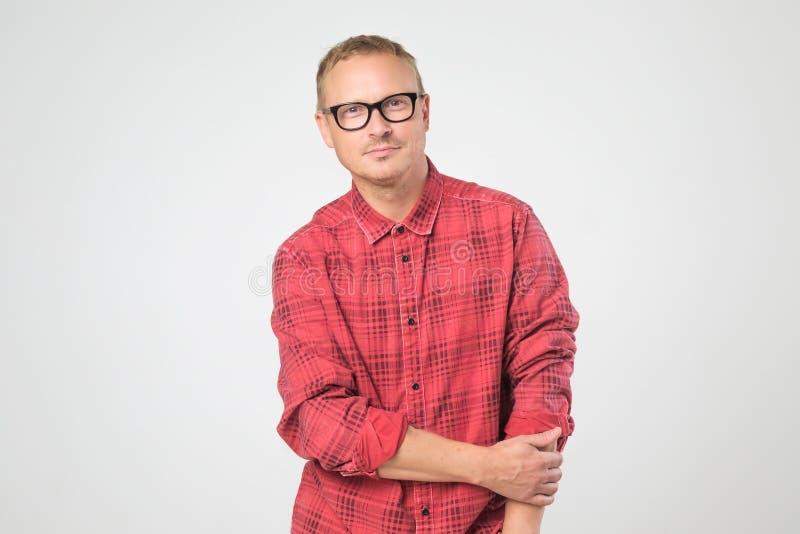 Homem maduro seguro nos vidros que vestem a camisa vermelha que olha a câmera imagem de stock