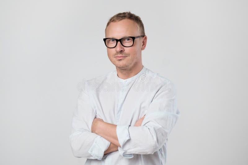 Homem maduro seguro nos vidros que vestem o t-shirt branco que olha a câmera imagem de stock