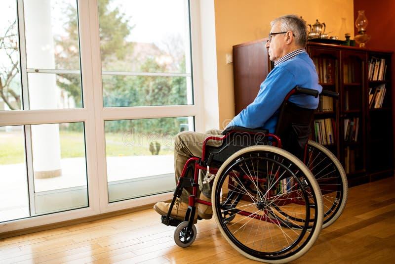 Homem maduro superior que senta-se na cadeira de rodas perto da janela em olhar o imagem de stock