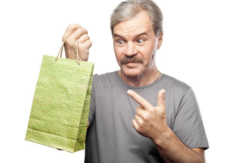Homem maduro surpreendido que mantém o saco de compras isolado no branco fotografia de stock royalty free