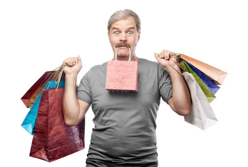Homem maduro surpreendido que mantem sacos de compras isolados no branco foto de stock