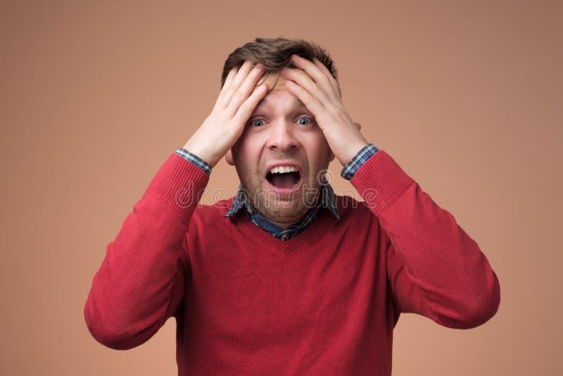 Homem maduro triste que guarda sua cabeça nas mãos e que grita fotografia de stock