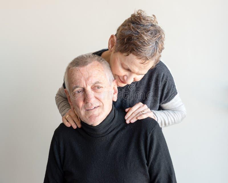 Homem mais idoso abraçado pela mulher mais idosa fotografia de stock