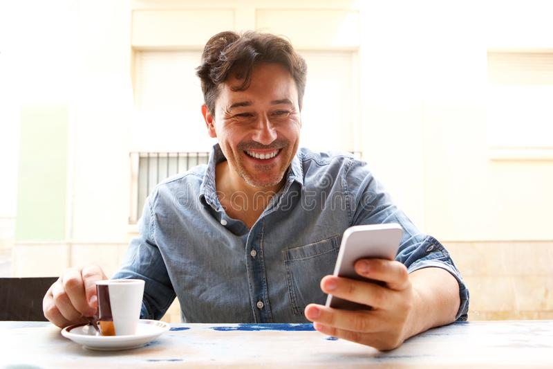 Homem mais idoso alegre com telefone e a xícara de café espertos imagens de stock royalty free