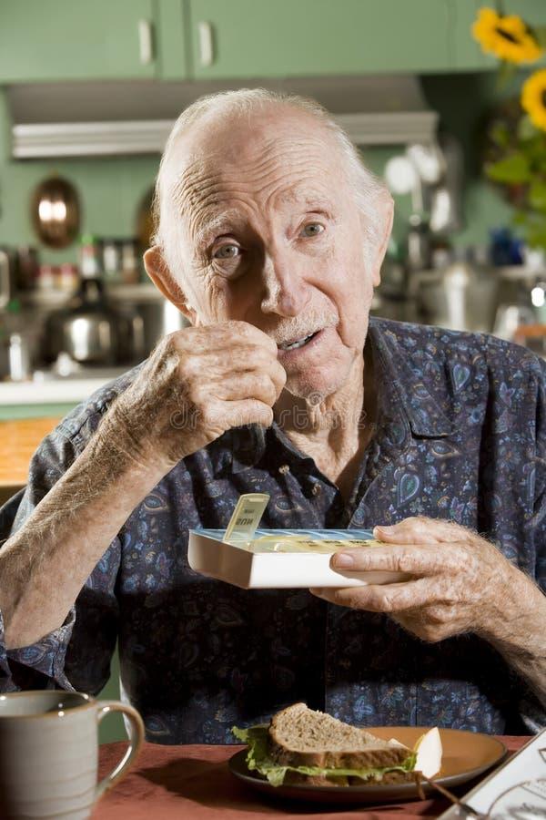 Homem mais idoso com uma caixa do comprimido imagem de stock