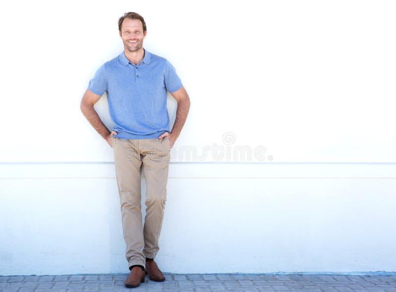 Homem mais idoso considerável do comprimento completo que sorri contra a parede branca foto de stock royalty free
