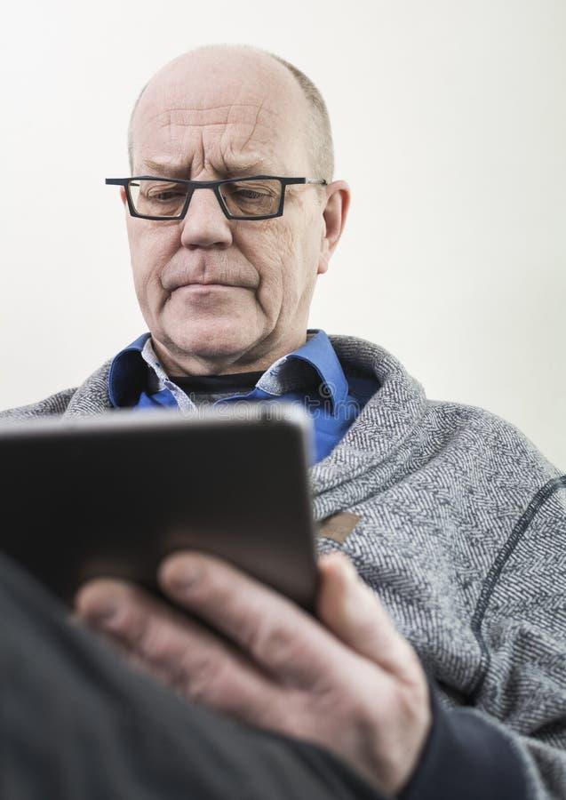 Homem mais idoso no PC da tabuleta fotos de stock