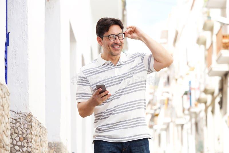 Homem mais idoso que anda fora com telefone celular e sorriso foto de stock royalty free