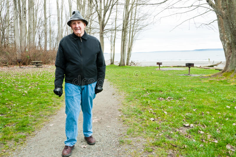 Homem mais idoso que anda no parque foto de stock royalty free