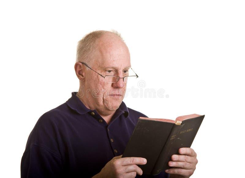 Homem mais idoso que lê atenta a Bíblia fotos de stock