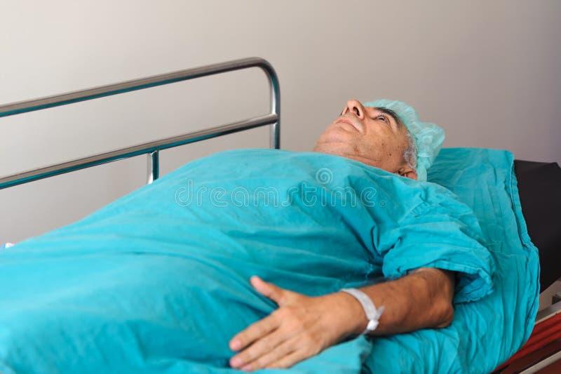 Homem mais idoso que prepara-se para submeter-se à operação da próstata no strecther imagens de stock