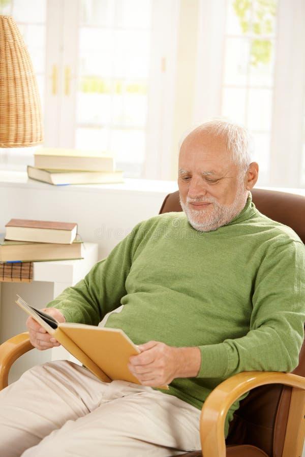 Homem Mais Idoso Que Relaxa Em Casa, Livro De Leitura Imagem de Stock Royalty Free