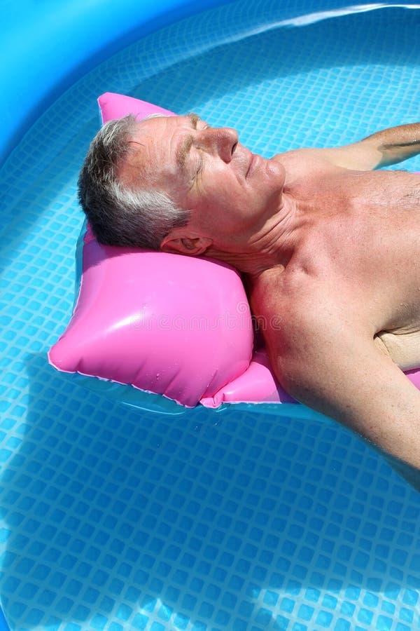 Homem mais idoso que sunbathing em um lilo fotografia de stock