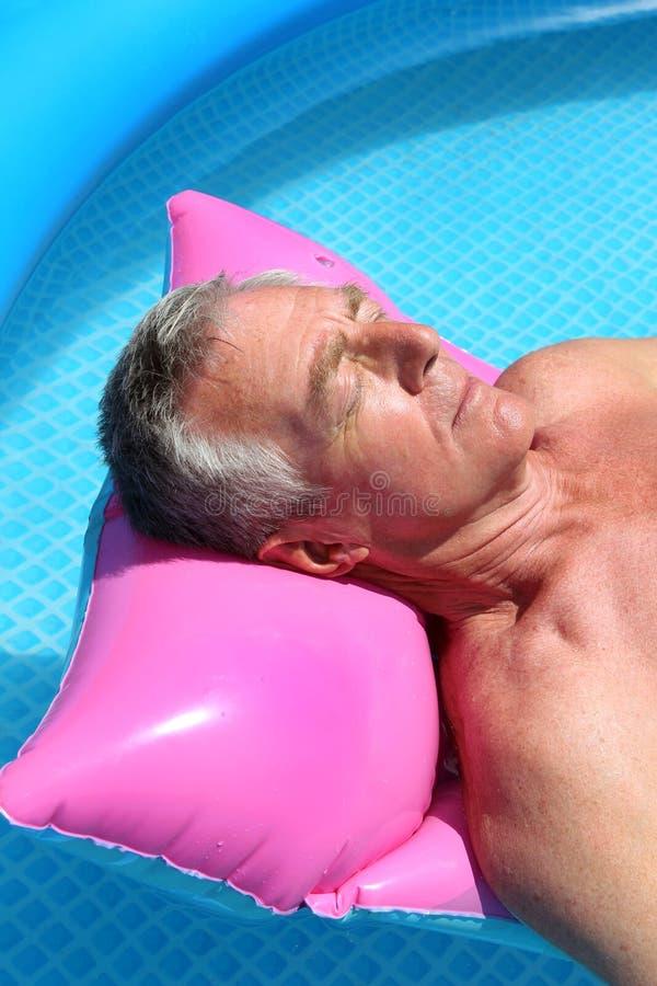 Homem mais idoso que sunbathing em um lilo foto de stock